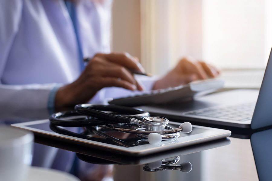 Health Savings Account - Practitioner Using a Calculator While Working on a Laptop with Stethoscope and Tablet on a Desk