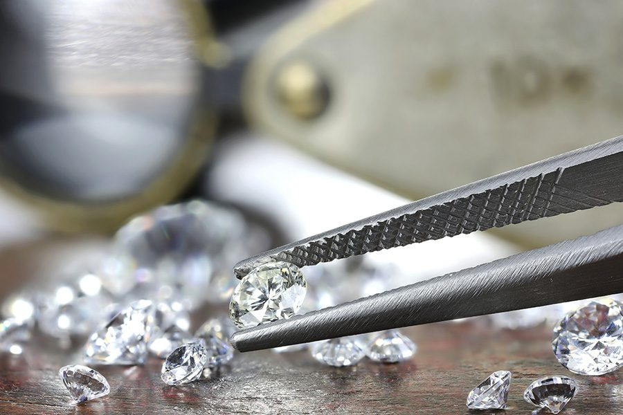 Jewelers Insurance - Closeup View of Brilliant Cut Diamond Held by Jeweler Using Tweezers