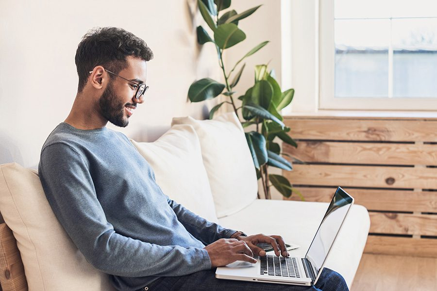 Resources - Handsome Young Man Working On His Laptop At Home On His Couch