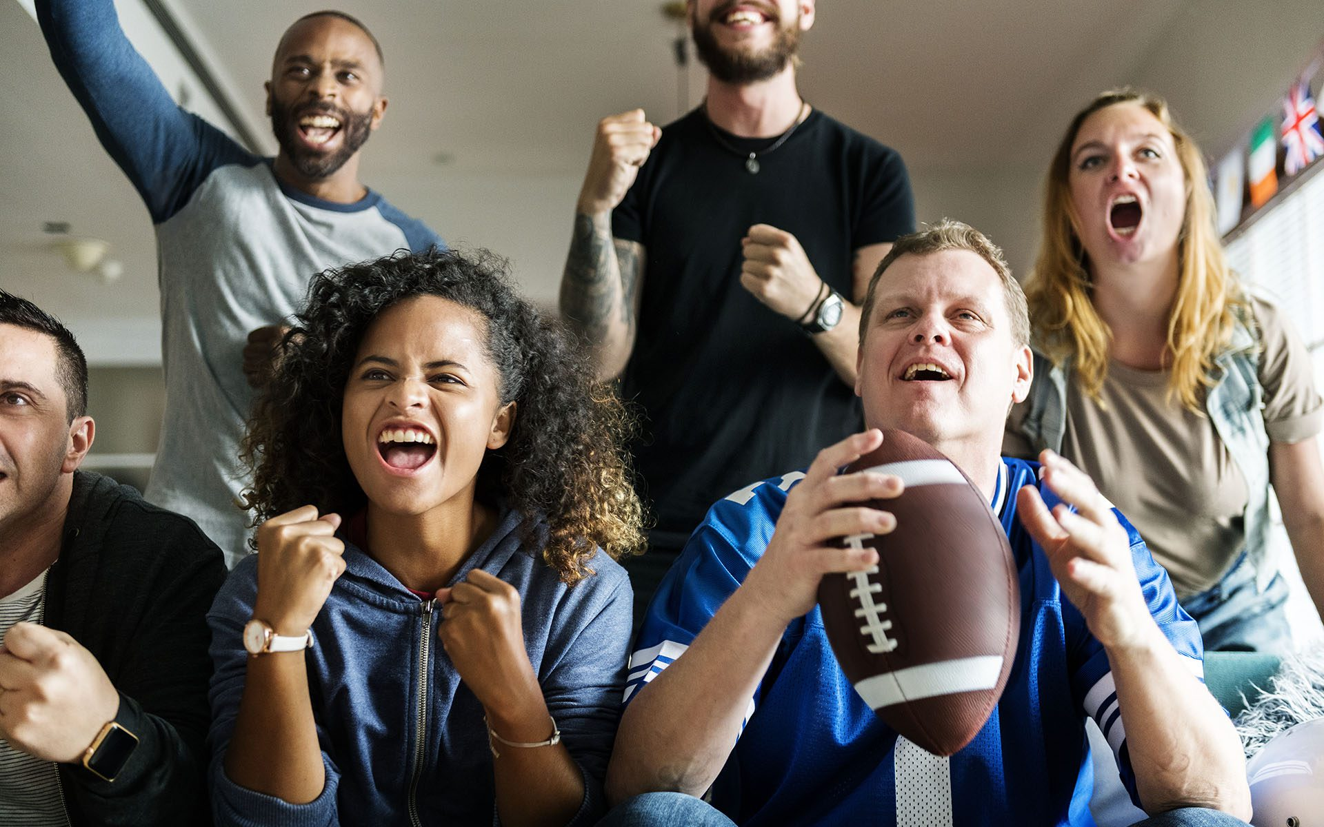Signed Penn State Football Giveaway - Football Fans Yelling and Smiling at the TV While the Game is on While They Sit on the Couch