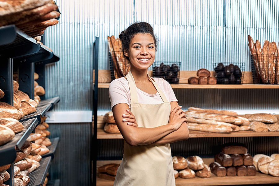 Business Insurance - Portrait of a Smiling Young Business Woman Standing in Her Bakery Surrounded by Fresh Bread