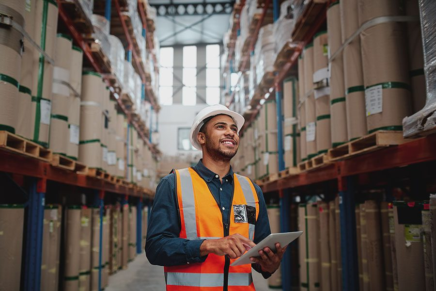 Specialized Business Insurance - Portrait of a Smiling Factory Worker Standing in a Manufacturing Facility With Packaged Products Holding a Tablet in His Hands