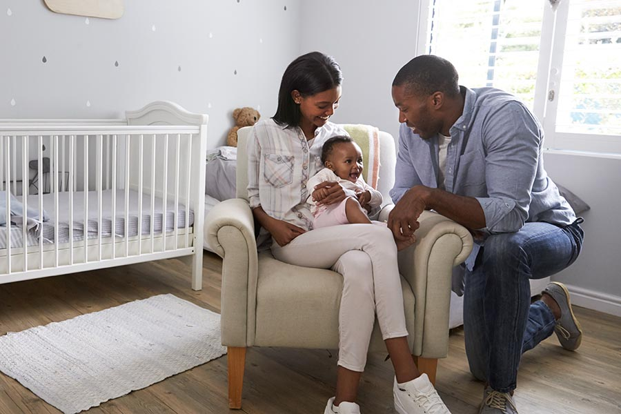 Personal Insurance - New Parents Play With Their Young Baby in Her Nursery, Decorated in Soft Gray Colors