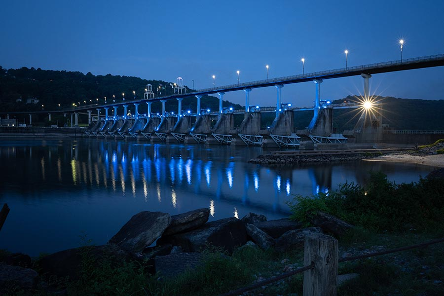 Searcy, AR Insurance - Night View Of a Bridge Over a River, Lit Up in Blue Lights Reflecting Off the Water