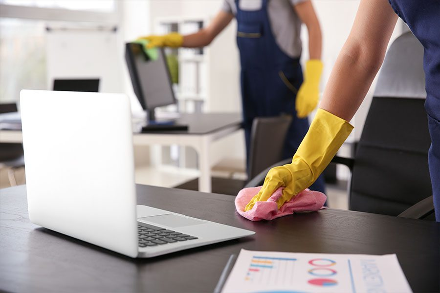 Janitorial Service Insurance - Janitors Cleaning Up a Desk Area After Business Hours