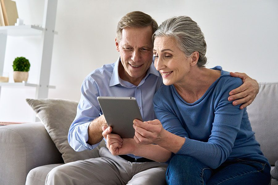 Client Center - Portrait of a Mature Couple Sitting on the Sofa in the Living Room Using a Tablet Together