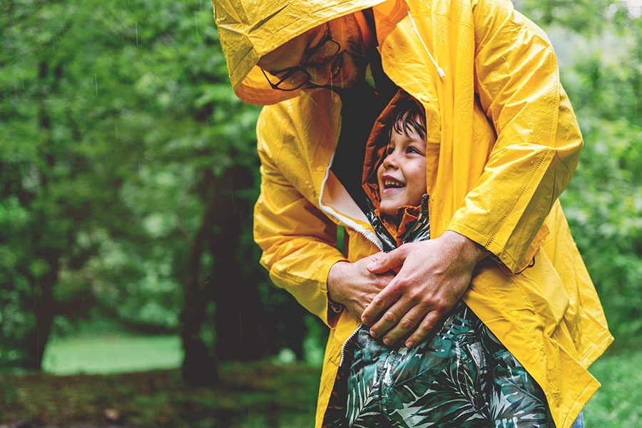 Contact - Closeup Portrait of a Father in a a Raincoat Hugging His Smiling Young Son as They Both Stand in the Rain in a Park