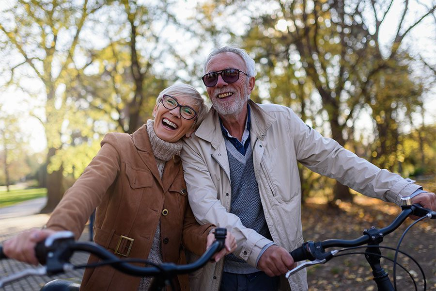 Employee Benefits - Portrait of a Cheerful Mature Couple Having Fun Riding Their Bikes in the Park During the Fall