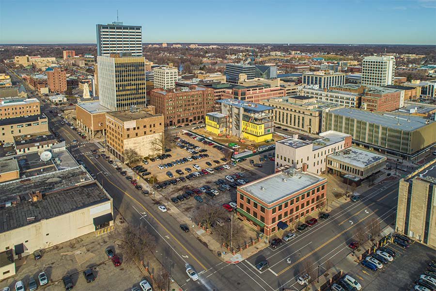 South Bend IN - Aerial View of Downtown South Bend Indiana with Views of Commercial Buildings and City Streets Against a Blue Sky