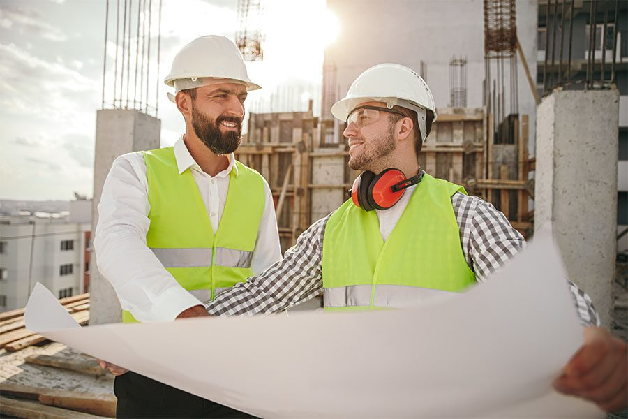 Specialized Business Insurance - Portrait of Two Smiling Contractors Looking at New Building Blueprints on a Commercial Construction Jobsite