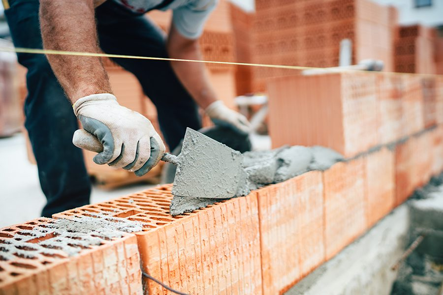 Masonry Contractor Insurance - Professional Masonry Worker Using Pan Knife for Building Brick Walls with Cement and Mortar