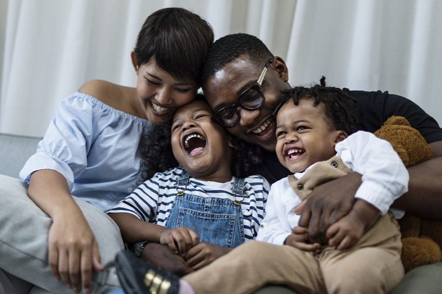 Employee Benefits - Happy Family Spending Time Together on the Sofa in the Living Room