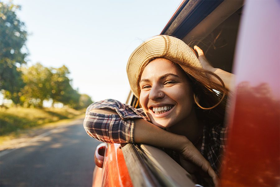 About Our Agency - View of a Cheerful Young Woman Sticking Her Head Out the Window from the Passenger Seat in a Car Enjoying the Fresh Air and Countryside Views