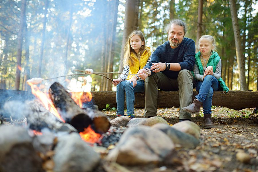 Blog - Father and His Two Daughters Sitting on a Log in the Woods During a Camping Trip Having Fun Toasting Marshmellows