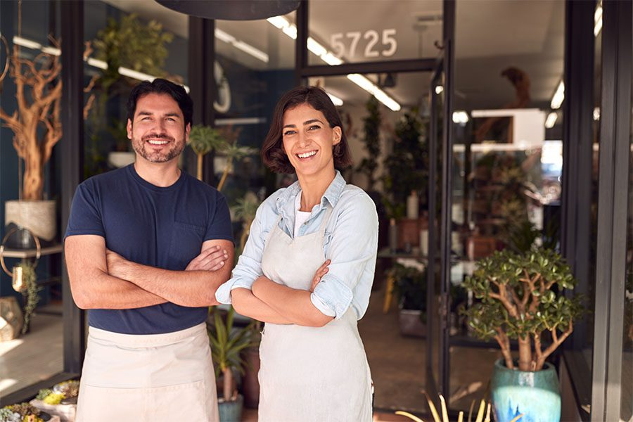 Business Insurance - Portrait of Two Cheerful Business Owners Standing Outside Their Flower Shop with Their Arms Crossed