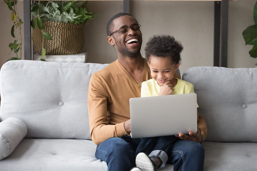 Client Center - View of Cheerful Father Sitting on the Sofa with His Son on His Lap in the Living Room While Using a Laptop