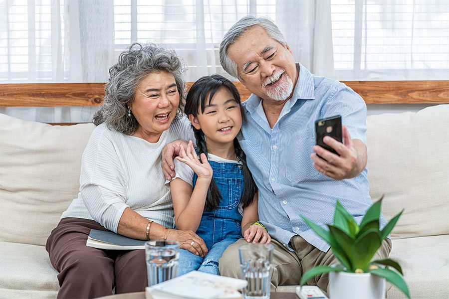 Contact - Cheerful Grandparents and Granddaughter Sitting on the Sofa Having Fun Using a Phone to Video Chat