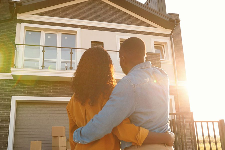 Personal Insurance - Rear View of a Young Couple Standing Outside Looking at Their New Home on a Sunny Day
