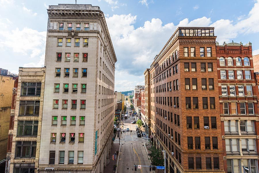 Contact Us - View of Downtown Pittsburgh, Tall Buildings Lining a Street, Blue Sky and Puffy White Clouds Overhead