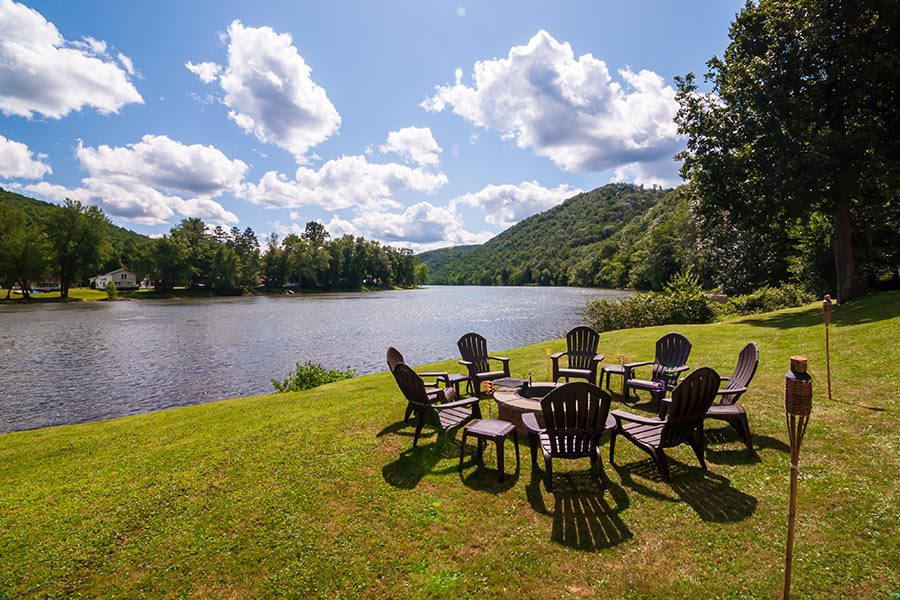 Monaca, PA Insurance - Adirondack Chairs on the Shore of a River, the Grass Green, Trees and Mountains in the Background