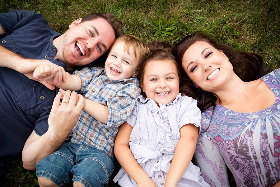Personal Insurance - Father, Two Small Children and Mother All Lay in the Grass, Heads Together, Laughing