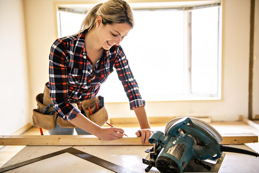 Specialized Business Insurance - Contractor Measures Lumber for a Home Renovation Project, a Circular Saw on Her Table