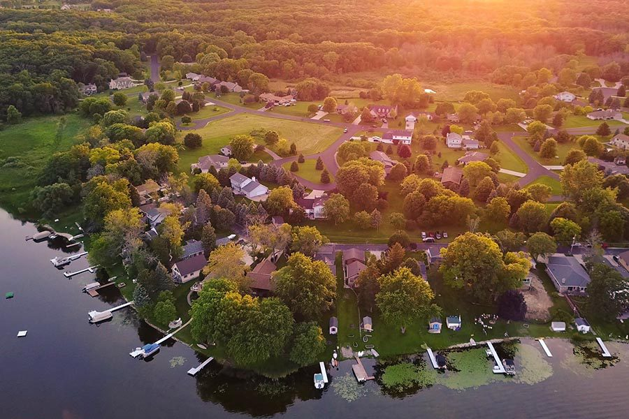About Our Agency - Aerial View of a Lakefront Community, Sun Setting Over the Trees