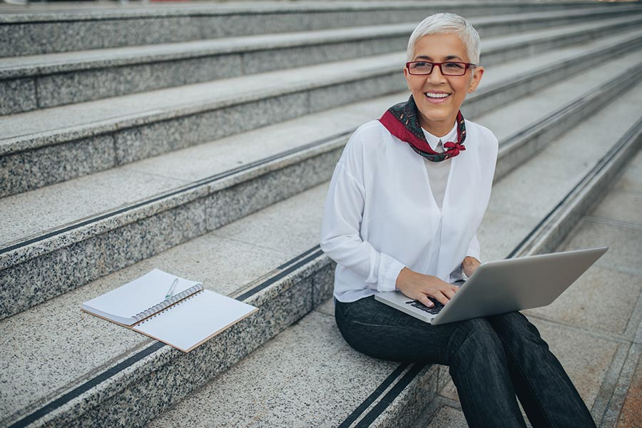 Client Center - Businesswoman Smiles and Sits on the Granite Steps of a Building, a Notebook by Her Side and Computer on Her Lap