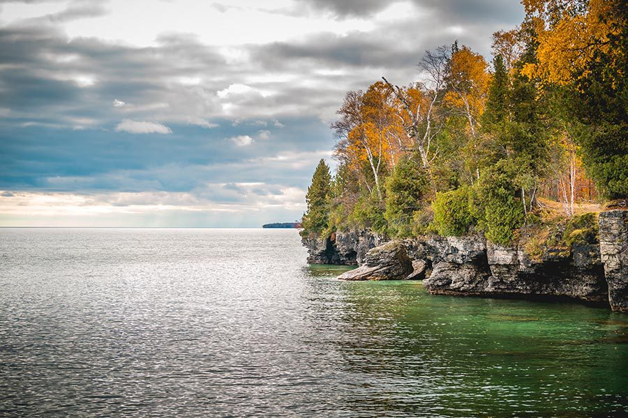 Contact Us - Fall Scene in Wisconsin, a Rocky Cliff Overlooking a Lake, Trees Turning Gold and Orange