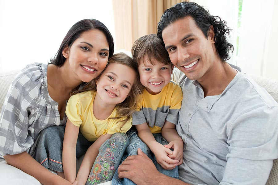 Personal Insurance - Mother, Father, Young Son and Daughter Cuddle in Close for a Family Photo, All Smiling, Dressed for Warm Weather