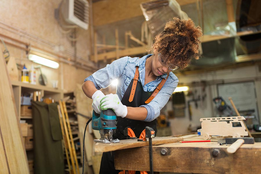 Specialized Business Insurance - Carpenter Works in a Large Wood Shop, Smiling and Wearing Safety Gear