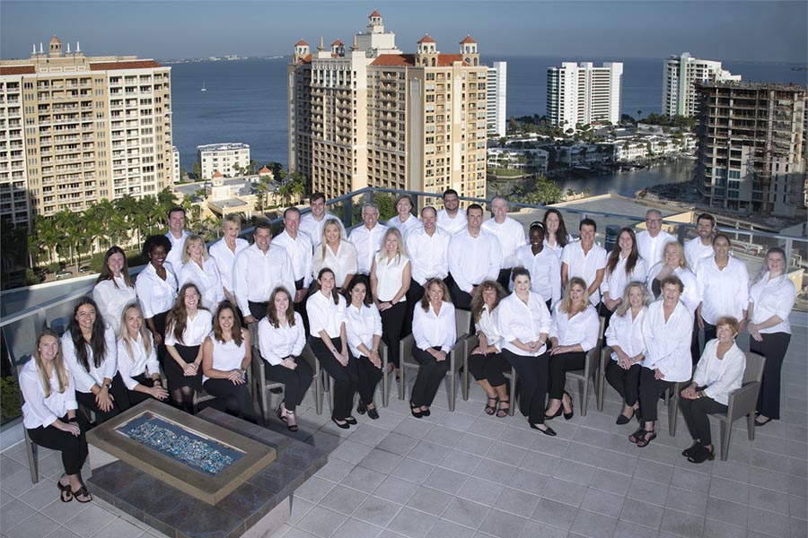 About Our Agency - Group Photo of Atlas Insurance Team Members Taken on a Stone Balcony Overlooking Sarasota Florida Buildings and Water