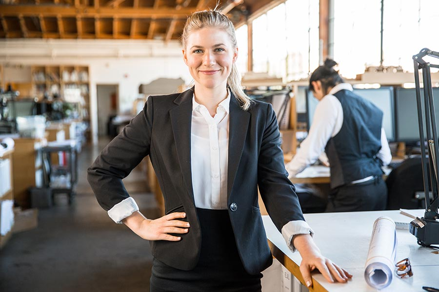 Business Insurance - Business Owner in a Garment Workshop Stands at a Worktable Wearing a Black Suit, Smiling