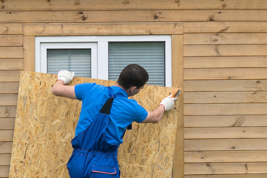 Hurricane Preparedness - Man in Gloves and Coveralls Boards up a Home's Windows, Preparing for a Storm
