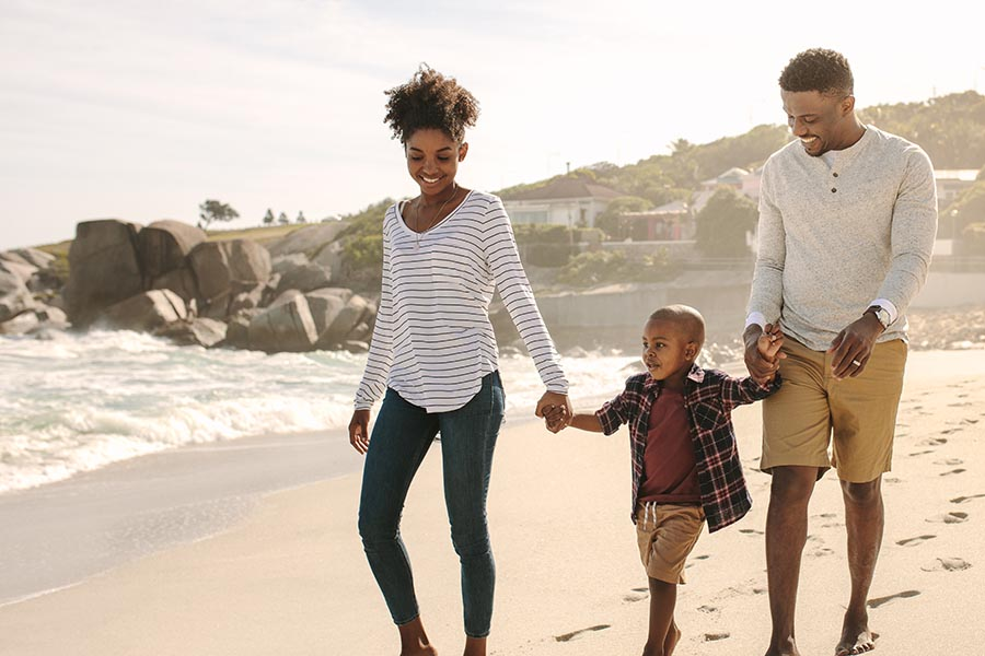 Personal Insurance - Family Smiles as They Walk Along the Beach on a Misty Afternoon, Parents Holding Their Young Son's Hands, Rocks and Surf Behind Them