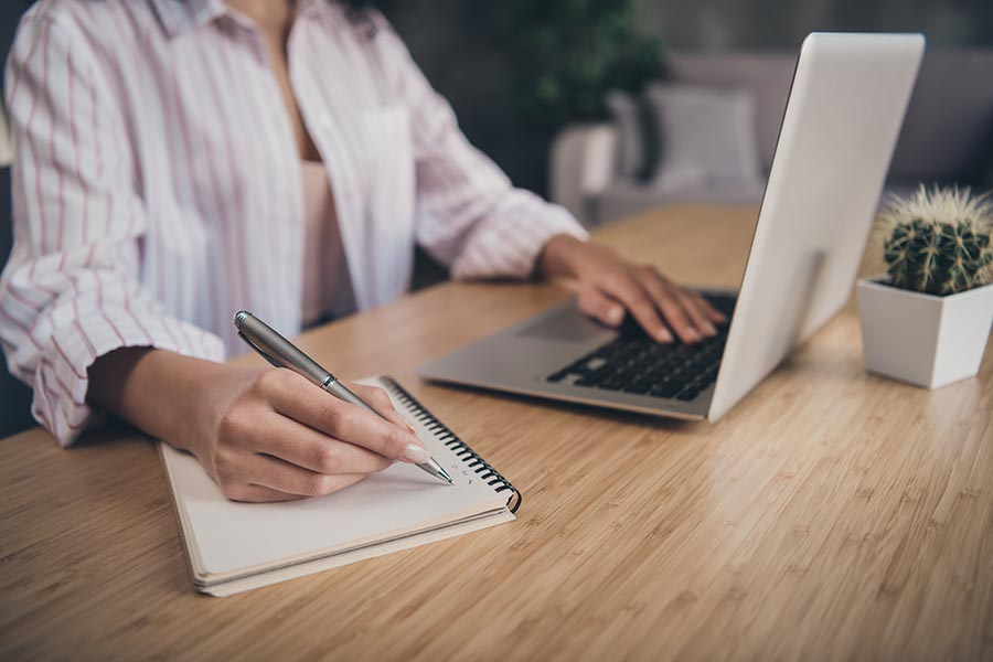 Resources - Woman Makes Notes in a Book While Using Her Laptop in a Home Office, a Small Cactus on Her Desk