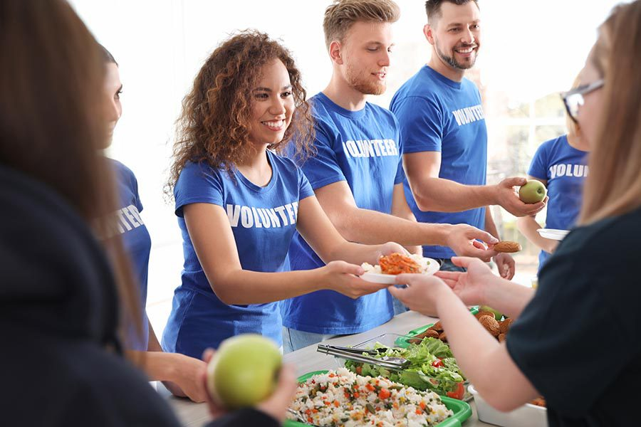 Specialized Business Insurance - Volunteers in Matching Blue Shirts Hand Out Meals During a Community Event
