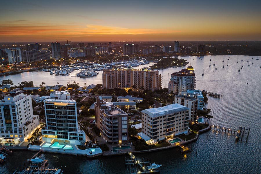 Contact Us - Aerial View of Sarasota, Florida Buildings at Night, Lights Glowing on the Water