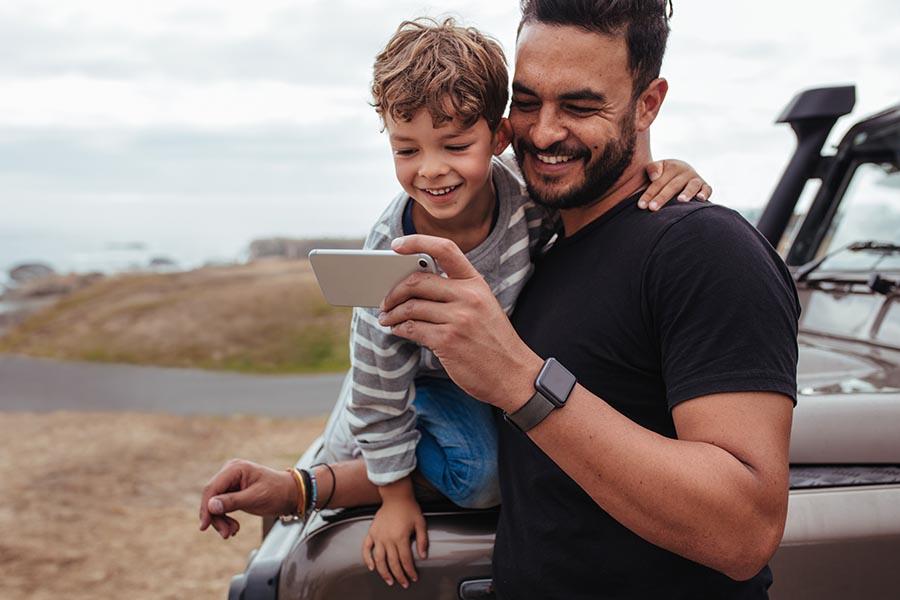 Blog - Dad and Young Son Use a Smartphone, Son Perched on the Hood of Their SUV, Both Smiling