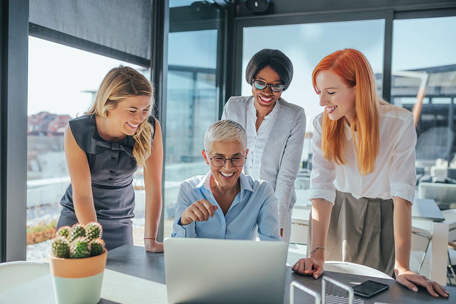 Business Insurance - Four Women in an Office With Large Windows Collaborate Around a Laptop, All Smiling
