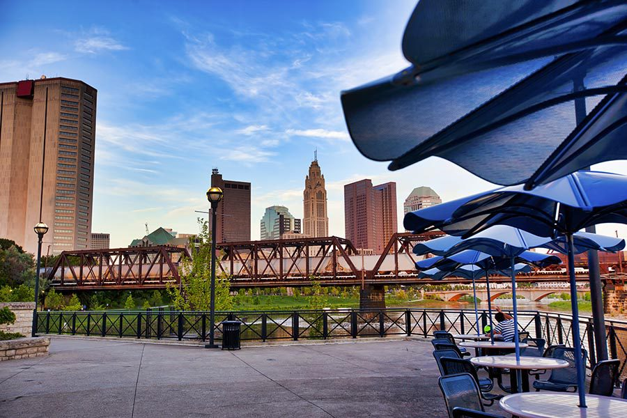 Client Center - a Patio at Northbank Park in Columbus, Ohio, Cafe Tables With Blue Umbrellas, the City Skyline, and a Train Passing