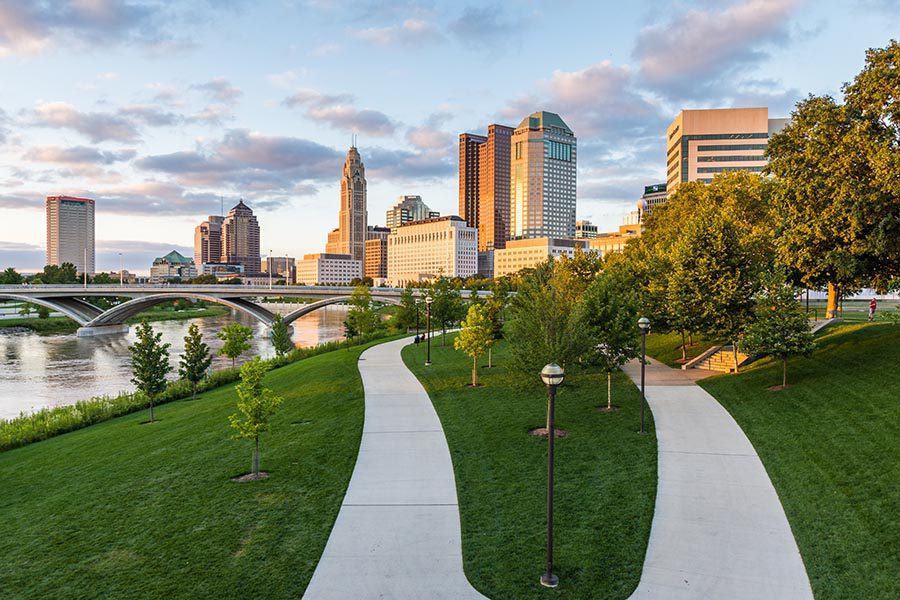 Columbus, OH Insurance - Paved Walking Paths in Columbus, Ohio, Surrounded by Green Grass, the River and Skyline Turning Orange in the Sunset