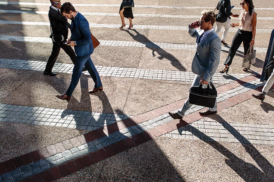 Contact - Busy People Cross a City Street, Dressed for Work, One Man Carrying a Briefcase and Using a Cell Phone