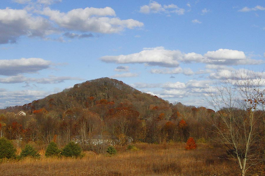 Lancaster, OH Insurance - Becks Knob in Lancaster, Ohio, a Large Mountain Set Against a Pale Blue Sky With White Puffy Clouds Above, the Landscape Turning Orange in Autumn