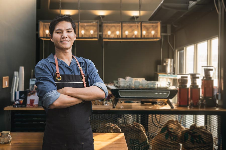 Specialized Business Insurance - Business Owner Stands in His Cafe Wearing a Work Apron, Arms Crossed and Smiling