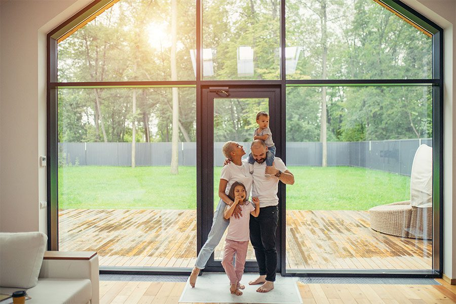 Blog - Portrait of a Family with Two Kids Standing in Their Living Room Next to a Full Length Glass Windows and Door with Views of the Patio and Green Backyard