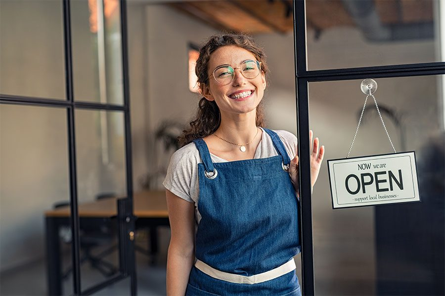 Business Insurance - Portrait of a Cheerful Young Female Business Owner Standing in the Entrance of Her Cafe Next to an Open Sign