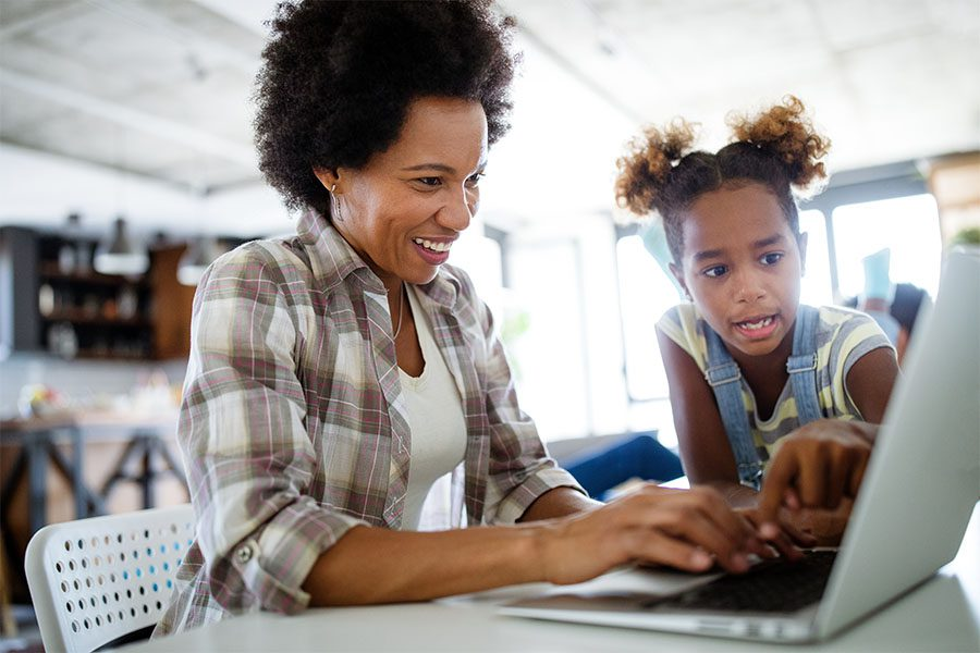Client Center - Closeup Portrait of a Cheerful Mother and Daughter Using a Laptop at Home