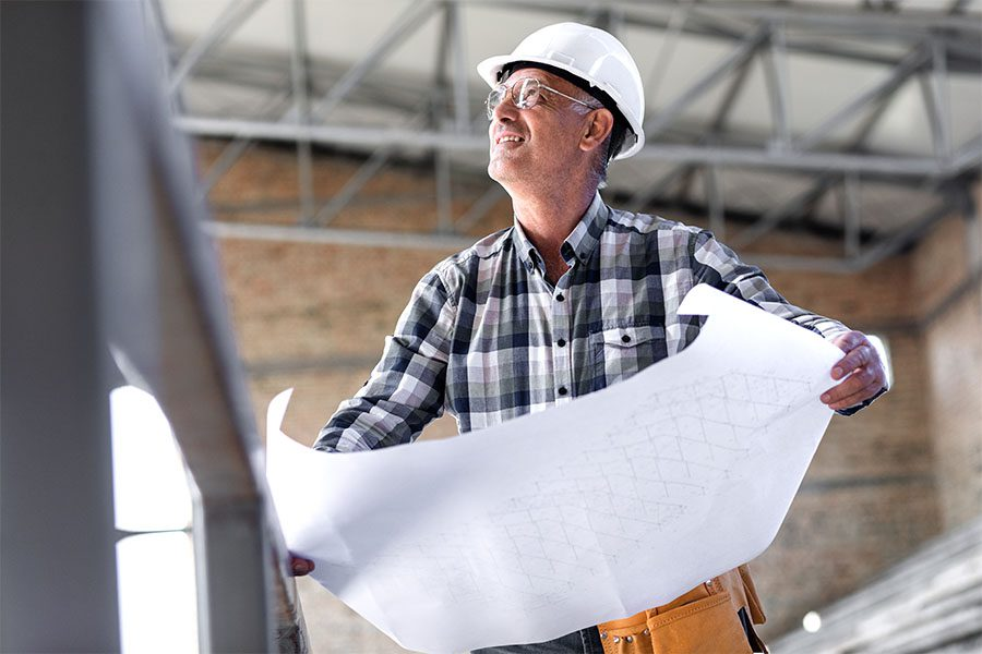 Specialized Business Insurance - Closeup Portrait of a Mature Contractor Holding Up New Building Blueprints While Standing on a Commercial Construction Jobsite
