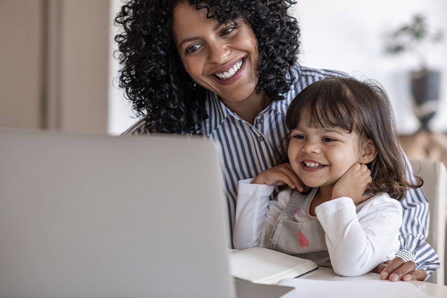 Blog - Busy Mother Using Her Laptop while Her Young Daughter is Sitting on Her Lap